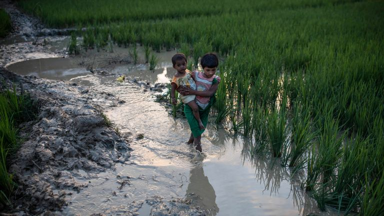 A young girl and a baby wade through mud after arriving from Myanmar in Whaikhyang, Bangladesh