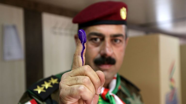 A member of a Kurdish Peshmerga battalion shows his ink-stained finger after casting his vote in the Kurdish independence referendum at a polling station in Arbil on September 25, 2017