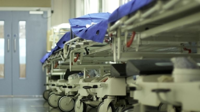 Hospital trolleys lined up in a corridor