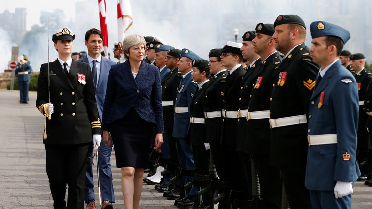 Theresa May inspects the honour guard with Canada's Prime Minister Justin Trudeau