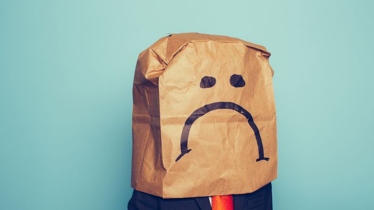 Young Businessman Wears Sad Face - Stock image - story on which workers are most unhappy