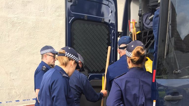 Police get digging equipment out during searches at a house in Thornton Heath