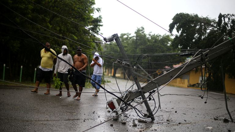 Locals walk past a fallen power pole as Hurricane Irma moves off the northern coast of the Dominican Republic