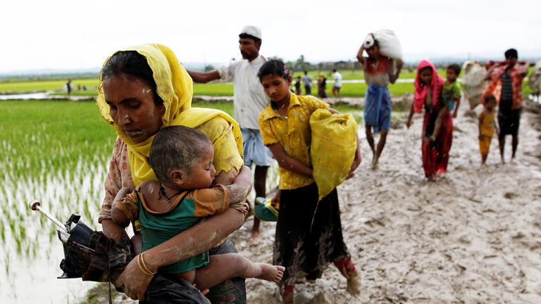 A Rohingya woman and her child travel to Bangladesh from Myanmar