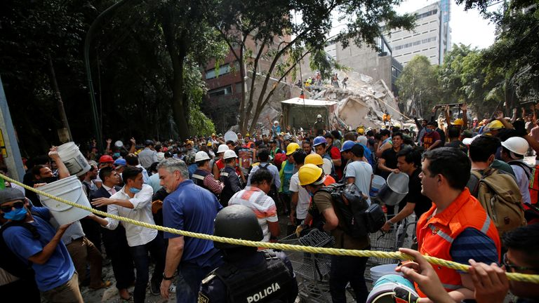 People carry buckets to help remove the rubble of a collapsed building