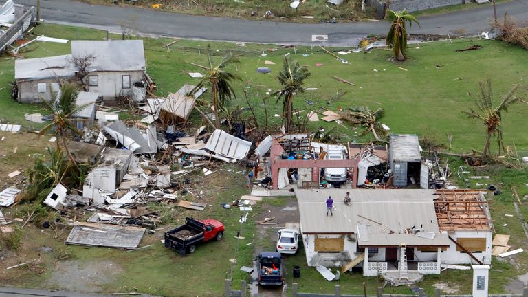 Residents work on their roof in a badly damaged neighbourhood in St. Croix, U.S. Virgin Islands