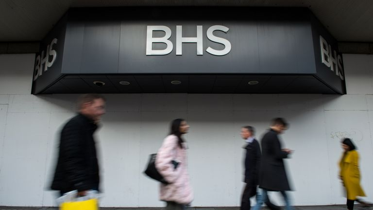 Shoppers walk past the boarded up BHS store on Oxford Street