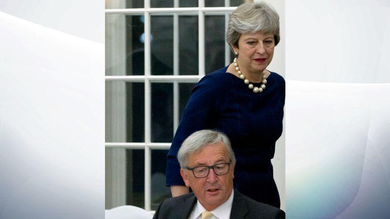 Theresa May walks past European Commission President Jean-Claude Juncker