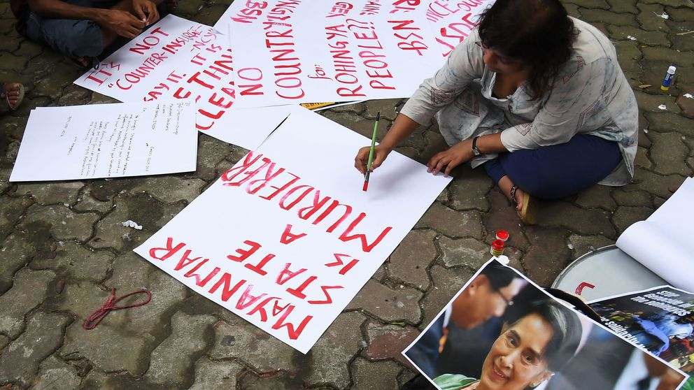 An student writes posters for a rally to protest the treatment of Rohingya Muslims in Myanmar, next to a picture of Myanmar's civilian leader and Nobel laureate Aung San Suu Kyi