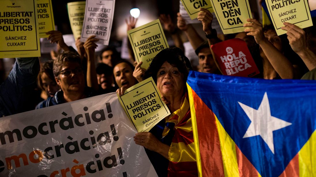 People hold Esteladas (Pro-independence Catalan flag) and papers reading in Catalan 'Freedom political prisoners' in front of the Generalitat Palace on October 17, 2017 in Barcelona. The demonstrators protested the judicial decision to imprison Spanish president of the Omnium Cultural, Jordi Cuixart, and Spanish president of the Catalan National Assembly (ANC), Jordi Sanchez. / AFP PHOTO / PAU BARRENA (Photo credit should read PAU BARRENA/AFP/Getty Images)