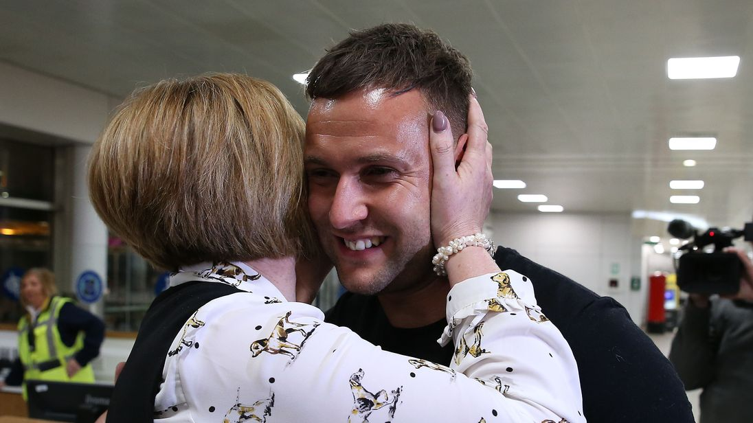 Jamie Harron, who was sentenced to three months in a Dubai jail for touching a man's hip, hugs his mother Patricia after arriving at Glasgow Airport