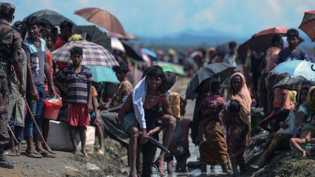 A Rohingya refugee carries an elderly man near the Myanmar-Bangladesh border