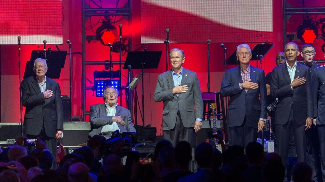 The five presidents listen to the national anthem