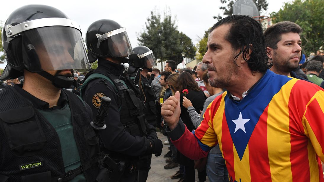 A man dressed in the Catalonian flag confronts officers