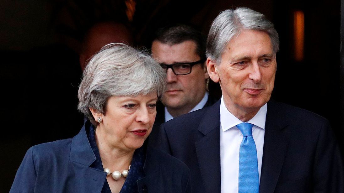 Theresa May and Philip Hammond leave their hotel at the Conservative Party's conference in Manchester