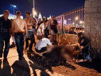 People tend to the wounded outside the festival ground