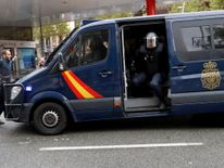 A demonstrator blocks a riot police van near a polling station for the banned independence referendum in Barcelona