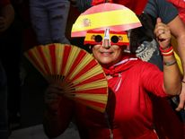 A woman wearing glasses and a hat in the colors of the Spanish flag gestures while attending a pro-union demonstration organised by the Catalan Civil Society organisation in Barcelona, Spain, October 8, 2017. REUTERS/Albert Gea