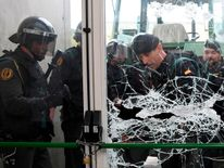 Spanish Guardia Civil guards brake the door of a polling station in Sarria de Ter