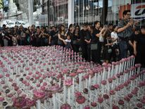 Mourners walking past an elaborate lotus flower display made in honour of the late king in Bangkok