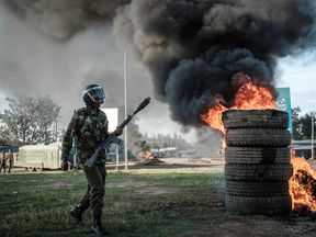 An anti-riot police officer near tyres set alight by opposition supporters in Kisumu