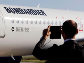 A man takes a picture of a Bombardier CSeries aircraft during a news conference to announce a partnership between Airbus and Bombardier on the C Series aircraft programme, in Colomiers near Toulouse, France, October 17, 2017