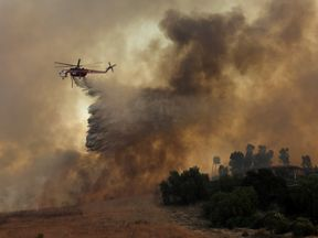 Helicopter drops water on California wildfires