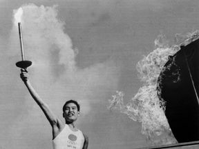 Yoshinori Sakai, who was born in Hiroshima on the day the first atomic bomb devastated the city, lights the Olympic flame in Tokyo's main stadium during the opening of the Olympic Games, 10th October 1964