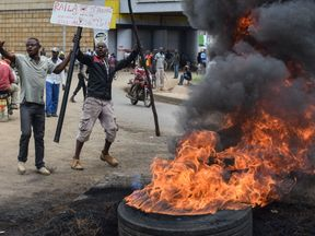 Supporters of Kenyan opposition coalition the National Super Alliance (NASA) protest next to a tire in fire in Kisumu