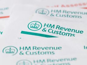 London, United Kingdom - July 6, 2016: HM Revenue and customs forms background with British currency coins. HMRC is the department of the UK government that is responsible for the collection of taxes.