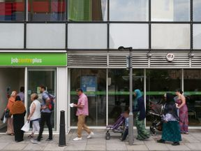 People queue to enter a job centre in east London