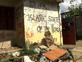 Graffiti proclaiming the 'Islamic State of the World' is seen on a building riddled with bullet holes