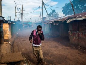 n opposition supporter reacts as Kenyan police spray teargas during clashes at the Kibera slum in Nairobi on October 26, 2017, after trying to block Olympic Primary polling station during Kenya's re-election voting. At least three people were shot dead on October 26 and more than 30 wounded as opposition protesters clashed with police during Kenya's presidential re-run, police and hospital sources said. / AFP PHOTO / Patrick Meinhardt (Photo credit should read PATRICK MEINHARDT/AFP/Getty Images)