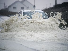 A motorist drives through sea foam whipped up by Storm Ophelia in Holyhead, north west Wales