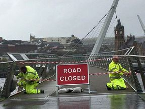 Staff from the Northern Ireland Road Service close the Peace Bridge in Londonderry, as Hurricane Ophelia hits the UK and Ireland with gusts of up to 80mph.