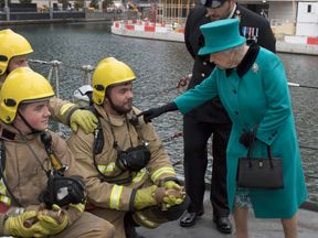 Queen presses firefighter's horn on HMS Sutherland.