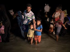 Boats full of people continue to arrive along the shores of the Naf River as Rohingya come in the safety of darkness September 30, on Shah Porir Dwip island, Cox's Bazar, Bangladesh