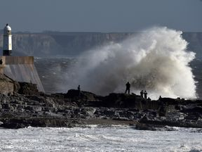 Waves crash over a lighthouse as Storm Ophelia approaches Porthcawl in Wales