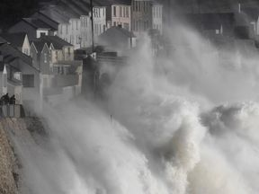 Large waves crash along sea defences and the harbour as storm Ophelia approaches Porthleven in Cornwall,...