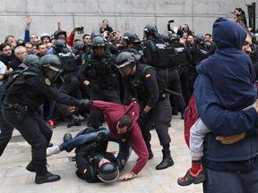 A man struggles with the police in Sany Julia de Ramis, near Girona