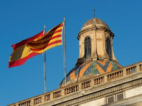 Spanish (L) and Catalan flags flutters atop the Generalitat Palace, the Catalan regional government headquarter in Barcelona, Spain, October 30, 2017. REUTERS/Yves Herman