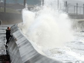Waves crash over the breakwater in Saltcoats on the west coast of Scotland