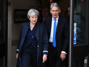 Theresa May and Philip Hammond leave the Midland Hotel on day two of the Tory party conference