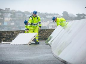 Temporary barriers being placed in Fowey, Cornwall, ahead of the arrival of Storm Brian
