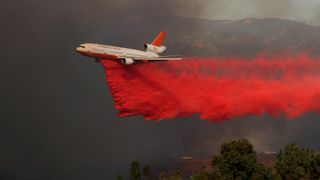 A DC-10 aircraft drops fire retardant on a wind driven wildfire in Orange, California