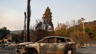 A burnt vehicle is see along Napa Road during the Nuns Fire in Sonoma, California