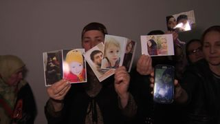 Russian women hold up images of their missing loved ones.