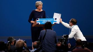 A member of the audience hands a P45 form to Theresa May