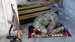 A member of Syrian Democratic Forces prays on his position during a battle with Islamic state militants in Raqqa