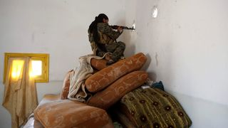 A fighter of Syrian Democratic Forces takes up a position inside a house in Raqqa